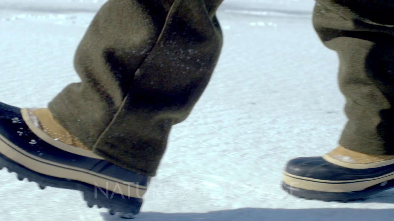 Snow boots walking across a snow-covered ground.